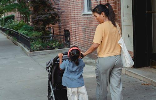 Ethnic mother helping daughter in carrying stroller